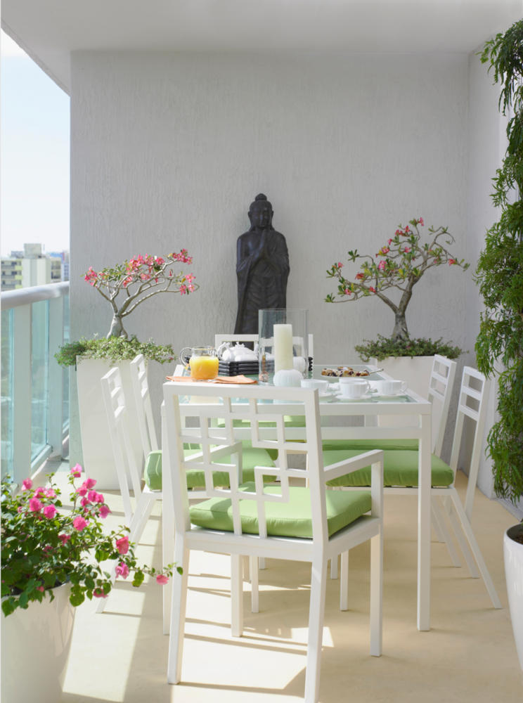 Food and drink laid on white table on balcony with pink flowering plants in pots